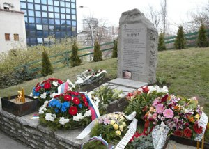 Flowers for the bombing's 16 victims are laid in front of a monument the 16 mourning families erected in Tasmajdan Park. The current RTS building can be seen in the background. Photo via B92.
