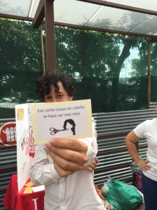 "One of my feminist friends holding up a picture which displays common sexist attitudes. It translates as ""That new haircut makes you look more old."""